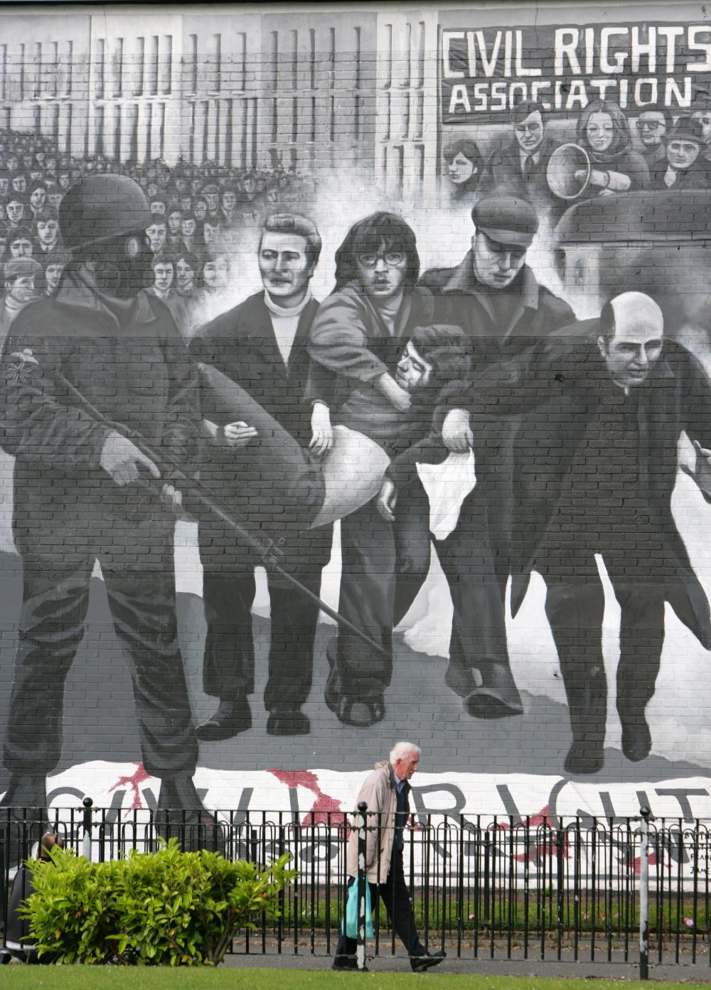 A man walks past a Bloody Sunday mural in the Bogside, Derry